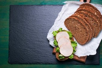Delicioso sándwich hecho en casa con hojas de ensalada y jamón en una tabla de cortar