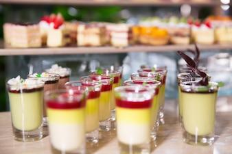 Deliciosos postres en vasos de chupito sobre mesa buffet