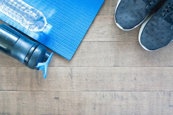 Deporte y equipo de entrenamiento sobre fondo de madera, plano de la disposición de concepto de estilo de vida saludable