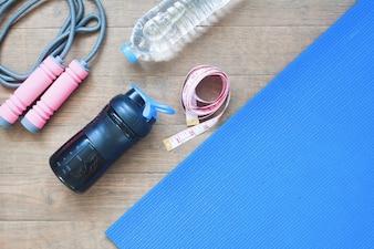Deporte y equipos de yoga con cinta métrica sobre fondo de madera con espacio de copia