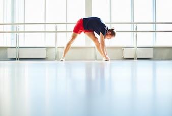 Deportista estirando las piernas antes de la sesión de entrenamiento