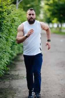 Deportista fuerte corriendo en el parque