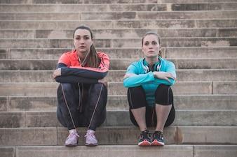 Deportistas sentadas con los brazos cruzados
