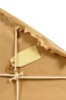Desgarrado paquete envuelto en papel marrón con etiqueta