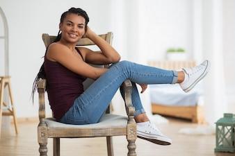 Despreocupado mujer africana sentada en un sillón