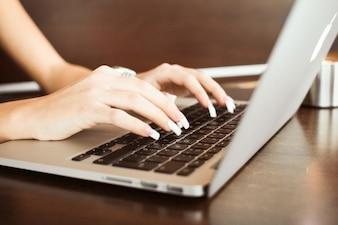 Detalle de la chica? s manos escribiendo en macbook