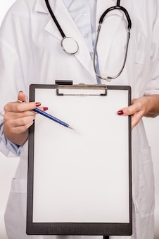 Detalle de un médico con estetoscopio sosteniendo un portapapeles
