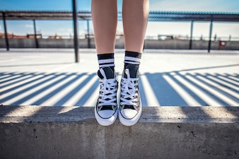 Detalles de las piernas de mujer de pie en la repisa de concreto en sus zapatillas clásicas