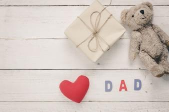 """Día de padre feliz de la vista superior. Corazón rojo con la palabra """"PAPÁ"""" en el fondo de madera. Presente y muñeca del oso para los regalos."""
