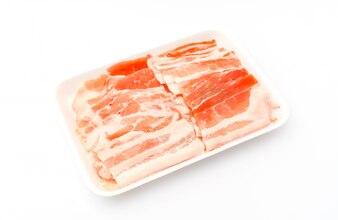 Diapositiva de carne de cerdo cruda sobre fondo blanco.