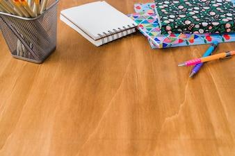Diarios y libreta con lápices y bolígrafos