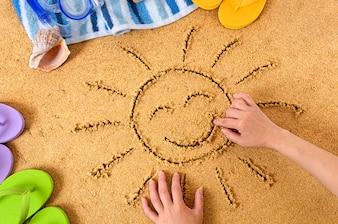 Dibujando un sol feliz en la playa