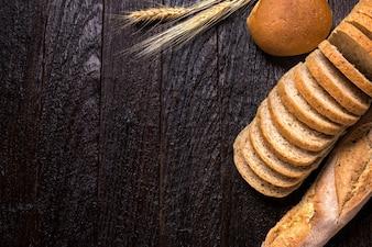 Diferentes panes frescos, en la vieja mesa de madera y copia espacio para texto, tono oscuro