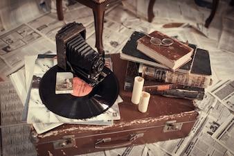 Disco de vinilo, con una cámara antigua y unos libros viejos