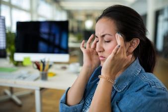 Diseñador gráfico femenina que sufre de dolor de cabeza