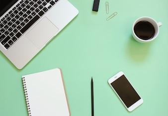 Diseño creativo plano de escritorio de espacio de trabajo con portátil, bloc de notas en blanco, smartphone, café, papelería con copia espacio de fondo