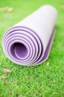 Doblado ejercicio, fitness o yoga mat en el césped