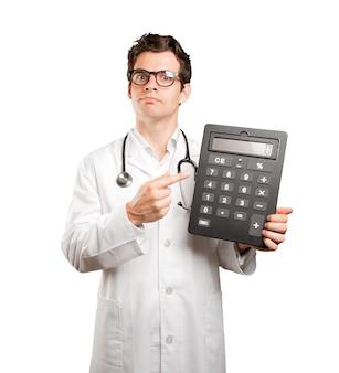 Doctor sosteniendo una calculadora preocupado por su economía contra el fondo blanco