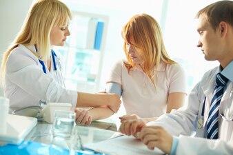 Doctora midiendo la presión arterial del paciente