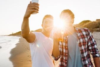 Dos amigos en la playa con puesta de sol