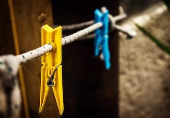 Dos diferentes clavos de lavado amarillo y azul colgando de la cuerda en el fondo de la vendimia.
