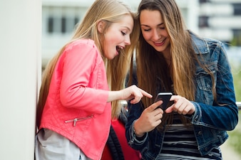 Dos estudiantes hermosos que usan el teléfono móvil en la calle.