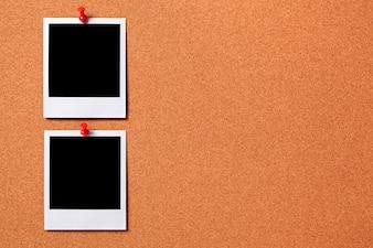Dos fotos polaroid clavadas en un tablero de corcho