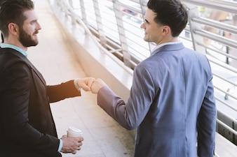 Dos hombres de negocios profesionales hablan y hacen topetón de puño en el área pública de la manera de la caminata