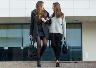 Dos joven empresaria caminando en la calle cerca de oficina buildi