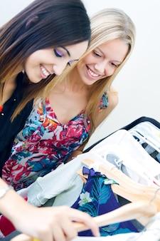 Dos jóvenes amigos en busca de ropa en la tienda