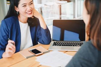 Dos jóvenes empresarias reunión y tomando sobre el proceso de trabajo en la oficina