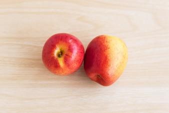 Dos manzanas están en la mesa de madera