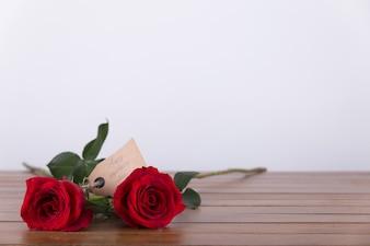 Dos rosas rojas con etiqueta en una mesa