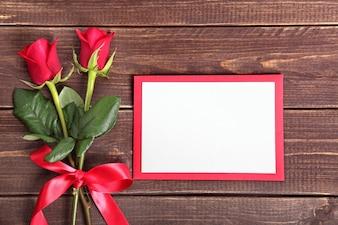 Dos rosas y una tarjeta para san valentín sobre madera