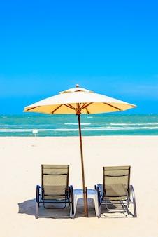 Dos sillas de la playa en la arena blanca