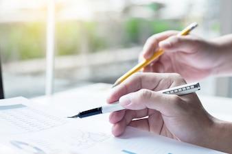 Dos socios de negocio que analizan un informe financiero que discute las estadísticas y el funcionamiento de su compañía.
