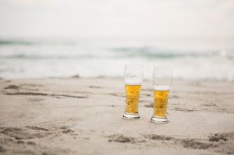 Dos vasos de cerveza mantienen en la arena