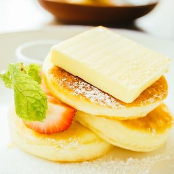 Dulce postre panqueque con mantequilla y fresa