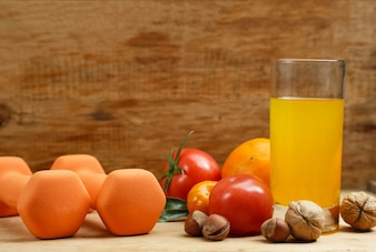 Dumbbell, jugo de naranja, frutas y nueces en la mesa de madera, deporte y concepto de estilo de vida de salud