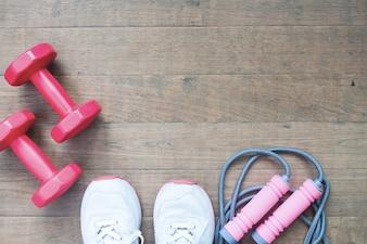 Dumbbells rojo, cuerda de salto y zapatos deportivos sobre fondo de madera con espacio de copia, concepto de estilo de vida saludable