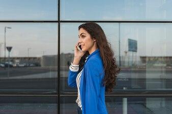 Ejecutiva joven hablando por teléfono con edificio de cristal de fondo