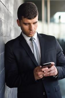 Ejecutivo guapo enviando un mensaje de texto