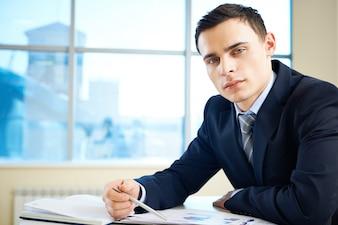 Ejecutivo guapo trabajando con informes comerciales