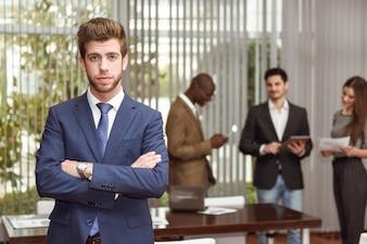 Ejecutivo joven con los brazos cruzados en el lugar de trabajo