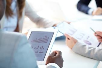 Ejecutivo sujetando una tableta digital con diagramas