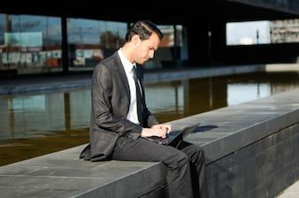 Ejecutivo usando su portátil al aire libre