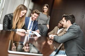 Ejecutivos sonrientes mientras analizan un documento financiero