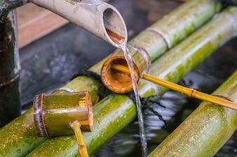 El agua que corre a través de la tubería de bambú.