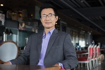 El hombre de negocios asiático de mediana edad en restaurante
