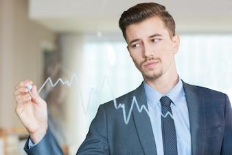El hombre de negocios serio dibujo gráfico de la tarjeta de cristal